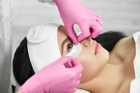Lashmaker is prepearing girl for lashes extension. Salon procedure of lashes enhancement. Professional wearing pink hygienic gloves. Client lying on special coach wearing headbandage for lashmaking.