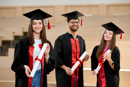 Positive graduates keeping diplomas standing in spacy modern university classroom. Students wearing new black and red graduation gowns. Feeling happy, satisfied, laughing. Having brilliant future.