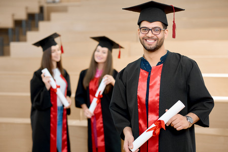 Happy smiling boy keeping university diploma. Graduate standing near young groupmates and looking satisfied. Students wearing black and red colored graduation gowns. Ending university.