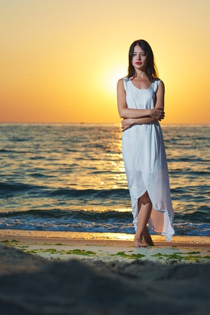 Wonderful girl wearing white long dress standing on sea sunset sideview. Deep blue sea waves behind her. Breezing fresh sea breeze. Watching on sun going down the horizon. Beatiful nature. Colors.