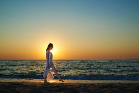 Photo of young stunning woman walking along the sea shore. Girl wearing long white dispersing on wind dress. Looking on deep blue sea and waves. Breezing fresh sea breeze. Watching on sun going down.
