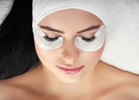 Portrait of girl lying during lashes enlarging. Woman with young beatiful face lying on special coach wearing headbandage for lashmaking. Having black hair, opened shoulders. Loving beaty procedures.