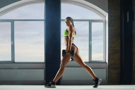 Sporty woman with strong body making exercises in spacy hall with panoramic windows. looks fit and stunning. Beatiful face, powerful muscles. Keeping big dumbbells. Wearing stylish sportswear.