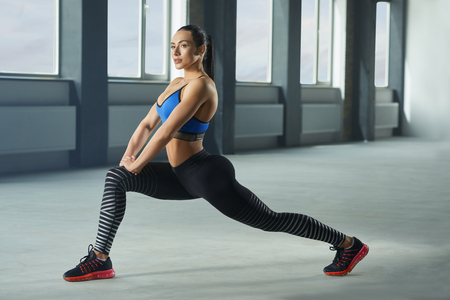 Young woman with athletic body doing fallouts in gym. Having sturdy muscles, healthy body and tanned skin. Looking strong, fit, feeling good. Wearing comfortable stylish sportswear.