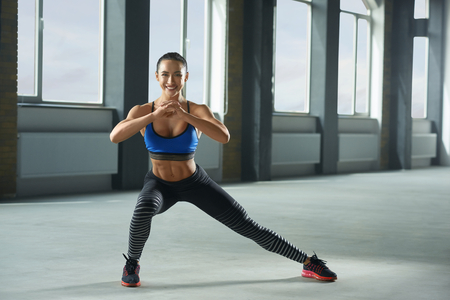 Frontview of young sporty girl with athletic body doing fallouts in gym. Having sturdy muscles, healthy body and tanned skin. Looking strong, fit, feeling good. Wearing comfortable stylish sportswear. Stock Photo
