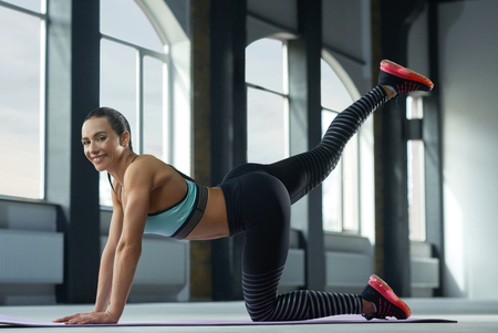 Sideview of sporty woman with strong body making exercises on spacy halls floor with panoramic windows. looks fit and stunning. Beatiful face, powerful muscles. Wearing stylish sportswear. 写真素材