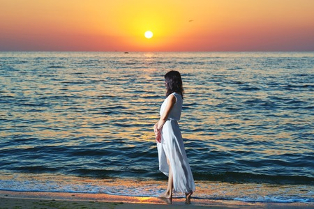 Girl wearing white summer dress standing on beatiful sunsets background. Looking on evenings deep blue sea and waves. Amazing, colorful sunset. Standing on sandy beach.