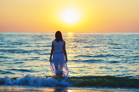 Backview of stunning woman wearing white long summer dress standing on beatiful sunsets background, walking on sea waves. Looking on evenings deep blue sea . Amazing, colorful sunset. Stock Photo