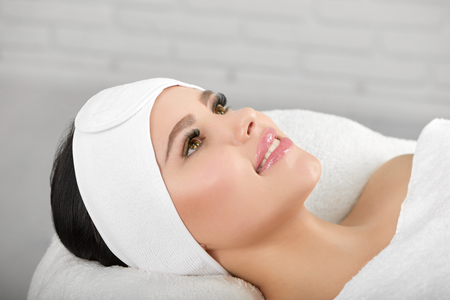 Smiling woman lying on white cosmetological coach wearing headbandage. Waiting for beaty salon procedures and professinal master. Smoth, young, healthy skin. Beatiful face.