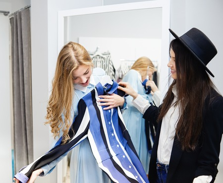 Two female friends trying on a blue and white stripped dress in shop. Wearing stylish, modern casual clothes. Having day light make up, blonde and brunette hair. Standing on white walls background. Фото со стока