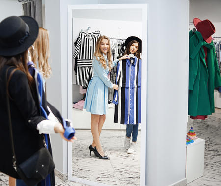 Female student wearing clack hat with fields and blue trying on stripped blue and white dress in the shop. Professonal seller wearing casual blue dress helping to choose. Clothes hanging on hangers. Фото со стока