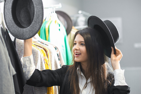 Smiling girl trying on stylish, modern black hats in clothing shop. Standing near colorful clothes hanging on hangers. Feeling good, looking positive, satisfied. Wearing white classic shirt, cardigan.