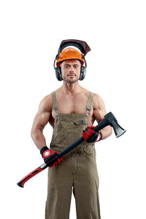 Photo of strong muscular man keeping an axe. Wearing khaki colored woodcutters. Looking fit, having sexy arms. Posing on white studio background. Concept of profession shooting.