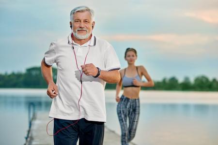 Älterer Mann, der Musik hört und am Abend nahe See läuft. Junges Mädchen läuft hinterher. Outdoor-Aktivitäten, gesunder Lebensstil, starke Körper, fit Figuren. Verschiedene Generationen. Sport, Yoga, Fitness
