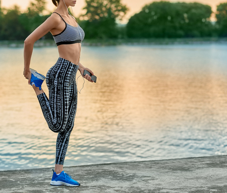 Cropped photo of girl making exercises on fresh air. Stretching, yoga, fitness. Model maintaining healthy lifestyle, sporty figure, nice appearance. Lake on background. Evening, beatiful nature.