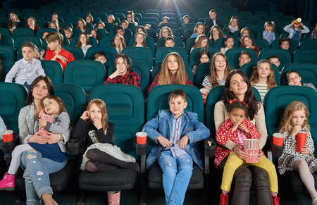 Young spectators sitting in modern movie theatre and watching cartoon. Teenagers and children sipping fizzy drinks and eating popcorn. Cute girls sitting on their moms laps. Project light source. Stock Photo