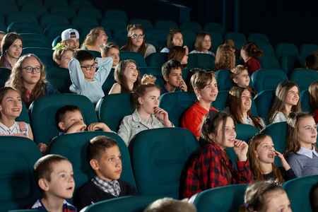 Group of stylish teenagers and children expressing facial emotions in movie theatre. Smiling spectators watching cartoon with steadfast eyes and sitting in comfortable blue chairs. Фото со стока
