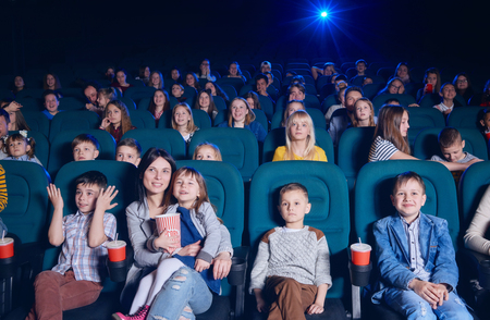 View of group of young people sitting in movie theatre, expressing emotions on their faces while watching film. Young spectators having fun, smiling. Project light source. Stock fotó