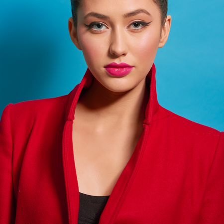 Contrast portrait of beatiful girl wearing red coat bright make up. Pink plump lips, pale cheeks, perfect eyebrow shape, big eyes, healthy skin color.Looking at camera, feeling confident. Imagens