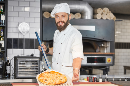 Front view of baker wearing chefs tunic and keeping pizza on metallic shovel. Working on spacy restaurants kitchen with big oven and wooden timbers behind. Man looking at camera, feeling happy.