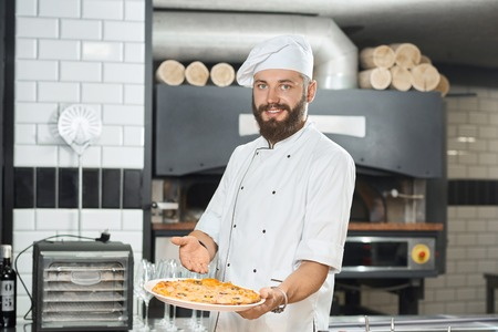 Smiling bearded pizzaiolo holding fresh baked mouthwatering pizza on big plate. Wearing white chefs tunic and a hat, working on restaurant kitchen with oven and alcohol bottles standing behind.