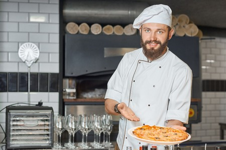 Happy pizzaiolo demonstrating fresh baked delicious pizza laying on big plate. Wearing white chefs tunic working on restaurant kitchen with oven, wooden timbers, wine glasses standing on background.