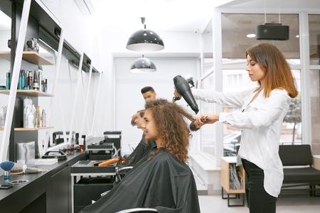 Vrouwelijke haarstylist krullend haar meisjes drogen met behulp van grote plastic borstel en elektrische droger. Het dragen van een wit casual overhemd en een zwarte broek met hoge taille. Client zit in de buurt van spiegel bedekt met zwarte cape.