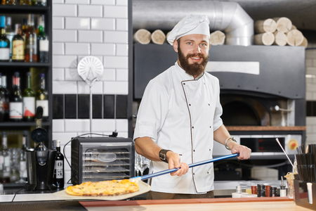 Smiling baker wearing white tunic keeping long metallic shovel with hot mouthwatering pizza. Having strong hands and dark brown beard. Working on kitchen with oven and alcohol bar behind. Banque d'images