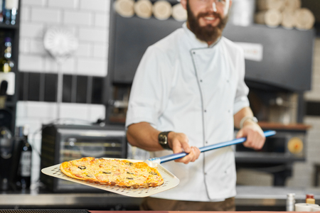 Cropped photo of smiling baker wearing white tunic keeping warm, fresh baked, delicious, mouthwatering pizza. Having strong hands and dark brown beard. Working on kitchen with oven and alcohol bar. Banque d'images