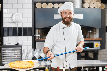 Smiling, happy baker keeping pizza on long blue metallic shovel, looking at camera. Wearing white chefs tunic and a cap,looking at camera. Working in restaurants kitchen with alcohol shelves nearby.