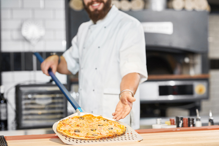 Cropped photo of baker holding fresh baked pizza laying on long metallic shovel. Smiling man wearing white chefs tunic, working on space restaurant kitchen with big oven and other equipment behind. Archivio Fotografico