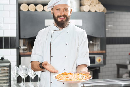 Smiling pizzaiolo holding fresh baked mouthwatering, delicious pizza. Wearing white chefs tunic working on restaurant kitchen with oven, wooden timbers, wine glasses set standing on background.