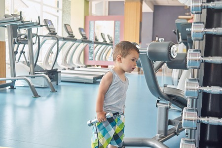 Little child standing in gym in front of metallic dumbbells and racetracks. Searching for father, looking dissapointed, interested, maintaining healthy lifestyle, cute face, big eyes, plump lips.