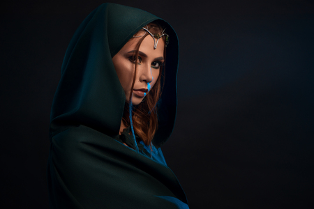 Beatiful elf princess wearing dark green cape, elegant crown decorated with precious stones, looking at camera from darkness. Girl having pretty face, big eyes, plump lips, long brown hair. Stock Photo