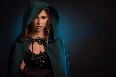 Mystic girl posing on dark studio background, wearing green cape, black corset. Model looking ar camera, having big eyes, brown curly hair. Looking like musterious elf queen.