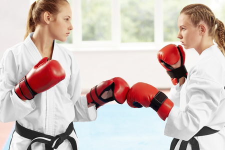 Close up of two female karate fighter standing in position ready to start fight against big window. Young athlete wearing in white kimono and red protective gloves, which they touching each other.