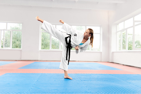 Sporty karate woman in white kimono with black belt against big window standing in karate position at fight class. Female fighter with blue eyes and braided hair improving technique of fight.