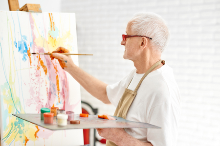 Side view of senior talented painter while painting his masterpiece at bright art studio. Handsome male artist, wearing in white t-shirt and apron and modern glasses drawing abstract picture on easel. Stock Photo