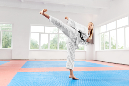 Sporty karate woman in white kimono with black belt against big window performing martial arts high kick at fight class. Female fighter with blue eyes and braided hair improving technique of fight.
