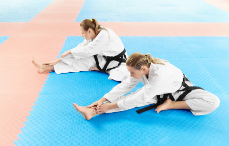 Two girl wearing in white kimono and black belts, training their flexibility before training in fight class. Young female karate sitting on floor and stretching their leg before training in light gym.
