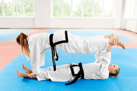 One girl laying on back on mate and holding her partner legs, other holding by arm legs of first, hanging all over her body above opponent. Young female karate stretching before training in light gym.