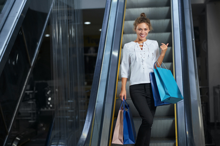 Front view of happy young woman with shopping bags enjoying new purchases in mall. Beautiful female customer looking at camera, posing and laughing on escalator. Concept of pleasure.