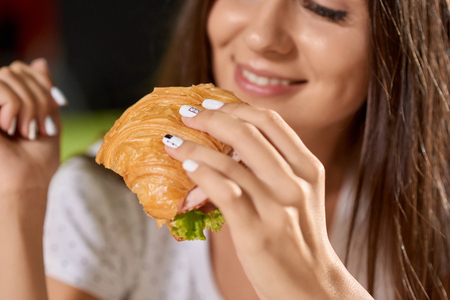 Closeup of tasty croissant with greens and ham in hands of pretty girl. Smiling woman keeping snack, eating and enjoying tasty food in cafe at background. Concept of delicious fast food.