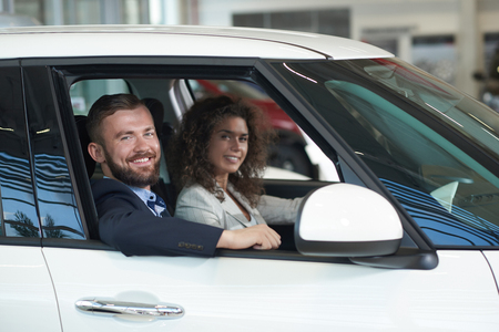 Couple sitting in white car, looking at camera and smiling. Bearded handsome man and pretty woman with curly hair observing car before buying. Husband and wife choosing auto in car center. Reklamní fotografie