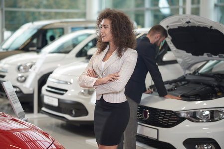 Curled happy woman walking in car store, when dealership looking inside automobile. Female client with curly hair choosing and observing cars for purchase. Manager working on background.