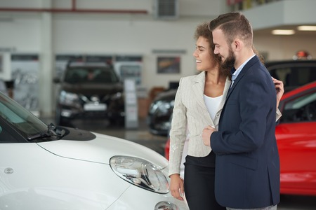 Happy couple standing in car center and choosing auto for purchase together. Handsome man in suit and beautiful woman with curly hair looking at cars and smiling. Vehicles placed on background.