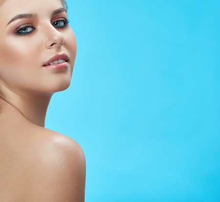 Close up of blond young pretty woman with professional make up and perfect eyebrows. Beautiful nude girl looking seductively at camera. Isolate of lady with naked shoulder on blue studio background. Stock Photo