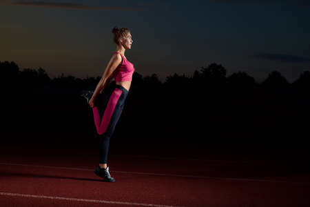 Side view of sporty young woman doing stretching for legs by hands after running. Curly athletic girl training at night alone at stadium, looking away. Concept of sport and yoga lifestyle.