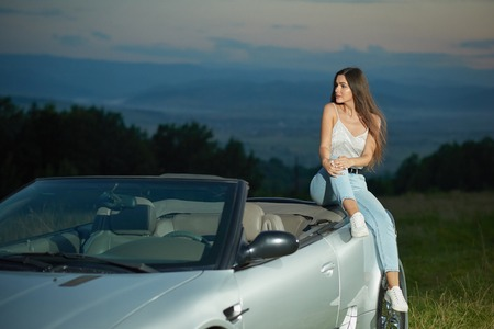 Charming model sitting on automobile and looking away. Young woman with chestnut hair posing on luxurious silver cabriolet. Girl wearing in jeans, white t shirt and sneakers.