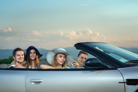 Happy couples  sitting in silver cabriolet, looking at camera and smiling. Charming, gorgeous women wearing white and dark blue broad brim hats. Friends driving car and enjoying weekends. 版權商用圖片